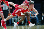 Wisconsin guard Brad Davison (34) tries to pass to a teammate as he falls to the floor during the second half of an NCAA college basketball game against Richmond in the Legends Classic, Monday, Nov. 25, 2019, in New York. Richmond defeated Wisconsin 62-52. (AP Photo/Kathy Willens)