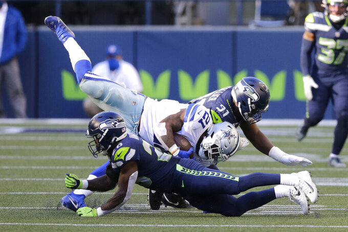 Dallas Cowboys running back Ezekiel Elliott goes down next to Seattle Seahawks safety Ugo Amadi (28) and defensive end L.J. Collier (91) during the second half of an NFL football game, Sunday, Sept. 27, 2020, in Seattle. The Seahawks won 38-31. (AP Photo/John Froschauer)