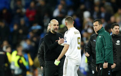 Manchester City's head coach Pep Guardiola, front left, shakes hands with Real Madrid's Karim Benzema at the end of the Champions League, round of 16, first leg soccer match between Real Madrid and Manchester City at the Santiago Bernabeu stadium in Madrid, Spain, Wednesday, Feb. 26, 2020. (AP Photo/Manu Fernandez)