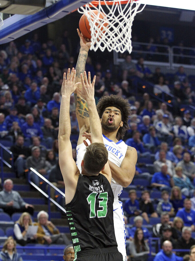 Kentucky's Nick Richards, right, shoots while defended by Utah Valley's Brandon Morley, left, during the first half of an NCAA college basketball game in Lexington, Ky., Monday, Nov. 18, 2019. (AP Photo/James Crisp)
