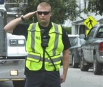 A police officer salutes as the procession honoring Farmington Fire Rescue Capt. Michael Bell as it arrives in Farmington, Maine, Tuesday, Sept. 17, 2019. Bell was killed in an explosion the day before that also injured six other firefighters and a maintenance worker at the LEAP building, a nonprofit that serves people with cognitive and intellectual disabilities in Farmington. (Rich Abrahamson/The Central Maine Morning Sentinel via AP)