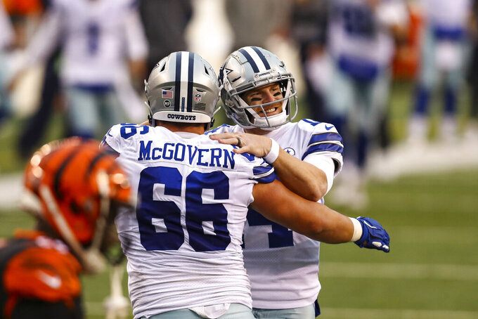 Dallas Cowboys quarterback Andy Dalton (14) celebrates a touchdown throw with offensive guard Connor McGovern (66) against the Cincinnati Bengals in the second half of an NFL football game in Cincinnati, Sunday, Dec. 13, 2020. (AP Photo/Aaron Doster)