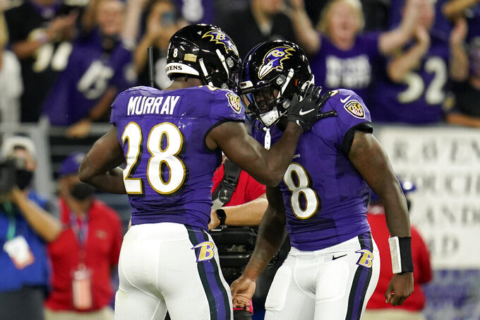 Baltimore Ravens running back Latavius Murray (28) celebrates his touchdown with quarterback Lamar Jackson in the first half of an NFL football gameagainst the Kansas City Chiefs, Sunday, Sept. 19, 2021, in Baltimore. (AP Photo/Julio Cortez)