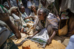 An Ethiopian woman argues with others over the allocation of yellow split peas after it was distributed by the Relief Society of Tigray in the town of Agula, in the Tigray region of northern Ethiopia, on Saturday, May 8, 2021. (AP Photo/Ben Curtis)