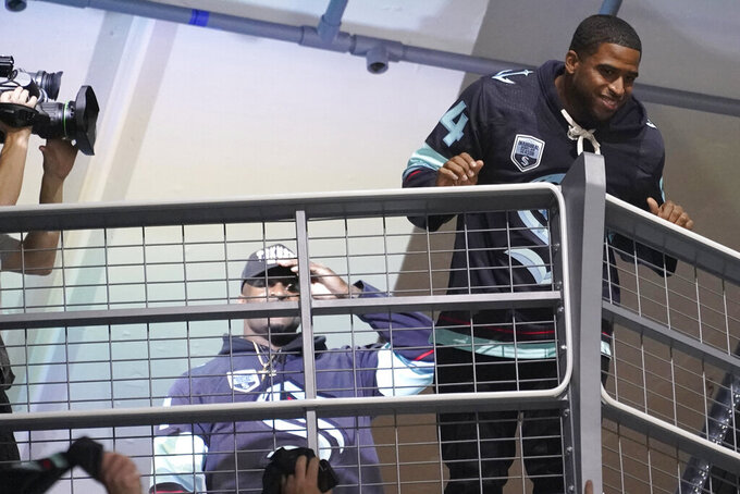 Seattle Seahawks' Bobby Wagner, right, and DK Metcalf, left, are introduced during an NHL hockey game between the Seattle Kraken and the Vancouver Canucks, Saturday, Oct. 23, 2021, in Seattle. (AP Photo/Ted S. Warren)