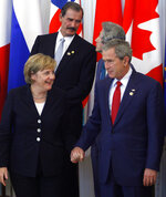 FILE - In this July 17, 2006 file photo, US President George W. Bush holds the hand of German Chancellor Angela Merkel during a group photo at the G8 Summit in St. Petersburg, Russia. Angela Merkel has just about seen it all when it comes to U.S. presidents. Merkel on Thursday makes her first visit to the White House since Joe Biden took office. He is the fourth American president of her nearly 16-year tenure as German chancellor. (AP Photo/Ivan Sekretarev, File)