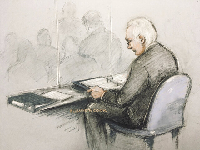 This is a court artist sketch of Wikileaks founder Julian Assange in the dock reading his papers as he appears at Belmarsh Magistrates' Court for his extradition hearing, in London, Monday, Feb. 24, 2020. The U.S. government and WikiLeaks founder Julian Assange will face off Monday in a high-security London courthouse, a decade after WikiLeaks infuriated American officials by publishing a trove of classified military documents.  (Elizabeth Cook/PA via AP)
