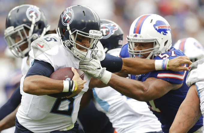Tennessee Titans quarterback Marcus Mariota (8) tries to get past Buffalo Bills outside linebacker Lorenzo Alexander (57) in the second half of an NFL football game Sunday, Oct. 6, 2019, in Nashville, Tenn. The Bills won 14-7. (AP Photo/James Kenney)
