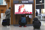 People watch a TV showing a file image of an unspecified North Korea's missile launch during a news program at the Seoul Railway Station in Seoul, South Korea, Thursday, Oct. 31, 2019. South Korea's military said North Korea on Thursday fired two projectiles toward its eastern sea, an apparent resumption of weapons tests aimed at ramping up pressure on Washington over a stalemate in nuclear negotiations. The sign reads: