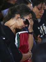 A relative holds the folded Mexican flag that covered the casket of her deceased loved one, one of the Mexican police officers killed in an apparent cartel ambush, during a memorial service in Morelia, Mexico, Tuesday, Oct. 15, 2019. The families of the 13 slain police officers gathered to mourn their loved ones outside a funeral home in the western state of Michoacan on Tuesday, many of them angry at the government and police chiefs they believe sent them to a certain death. (AP Photo/Marco Ugarte)