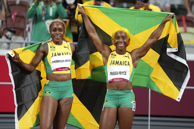 Elaine Thompson-Herah, left, of Jamaica, celebrates after winning the women's 100-meters final with teammate Shelly-Ann Fraser-Pryce at the 2020 Summer Olympics, Saturday, July 31, 2021, in Tokyo. (AP Photo/Matthias Schrader)