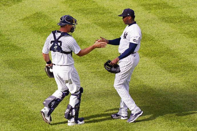 New York Yankees catcher Erik Kratz, left, shakes hands with relief pitcher Aroldis Chapman after Chapman earned a save in a victory over the Baltimore Orioles in a baseball game, Sunday, Sept. 13, 2020, at Yankee Stadium in New York. (AP Photo/Kathy Willens)