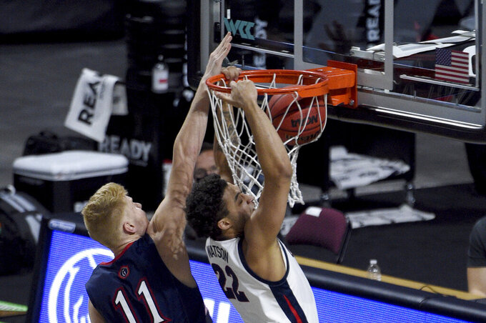 Gonzaga forward Anton Watson (22) dunks against Saint Mary's forward Matthias Tass during the second half of an NCAA semifinal college basketball game at the West Coast Conference tournament Monday, March 8, 2021, in Las Vegas. (AP Photo/David Becker)