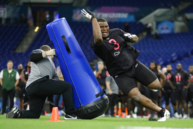 """FILE - In this Feb. 29, 2020, file photo, Auburn defensive lineman Derrick Brown runs a drill at the NFL football scouting combine in Indianapolis. Atlanta Falcons  coach Dan Quinn says the NFC South """"is turning into Quarterback South."""" The priority to """"bring it"""" on defense was evident in the NFL draft. (AP Photo/Michael Conroy, File)"""