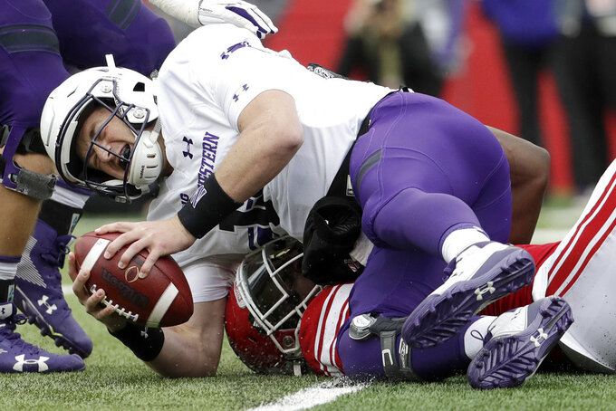 Northwestern quarterback Clayton Thorson, top, is sacked by Rutgers defensive lineman Elorm Lumor during the first half of an NCAA college football game, Saturday, Oct. 20, 2018, in Piscataway, N.J. (AP Photo/Julio Cortez)