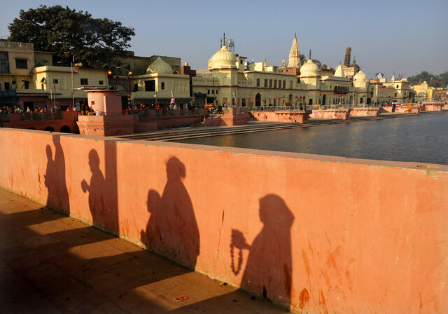 FILE-In this Nov. 11, 2019 file photo, Hindu devotees pray while walking towards a temple, in Ayodhya, India. India's Prime Minister Narendra Modi will attend a groundbreaking ceremony next month for a Hindu temple on a disputed site in northern India where a 16th-century mosque was torn down by Hindu hard-liners in 1992. The trust overseeing the temple construction says the ceremony is set for Aug. 5, a date they say is astrologically auspicious for Hindus but that also marks a year since the Indian Parliament revoked the semi-autonomous status of its only Muslim-majority state, Jammu and Kashmir. (AP Photo/Rajesh Kumar Singh, File)
