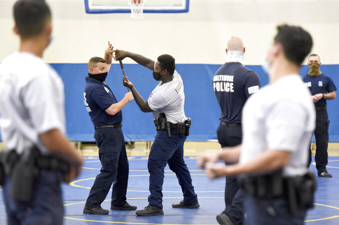 Baltimore city police instructor Mike Long, left, demonstrates a technique with police trainee Alhaji Fofana, center, of Philadelphia, during defense tactic training, Wednesday, Aug. 4, 2021, in Baltimore. Baltimore's police force is struggling to meet staffing targets to fully comply with a reform intervention and get out from under federal oversight. The agency has some 400 vacancies among its sworn staff and its recruitment efforts just can't keep pace with those leaving their jobs. (AP Photo/Steve Ruark)