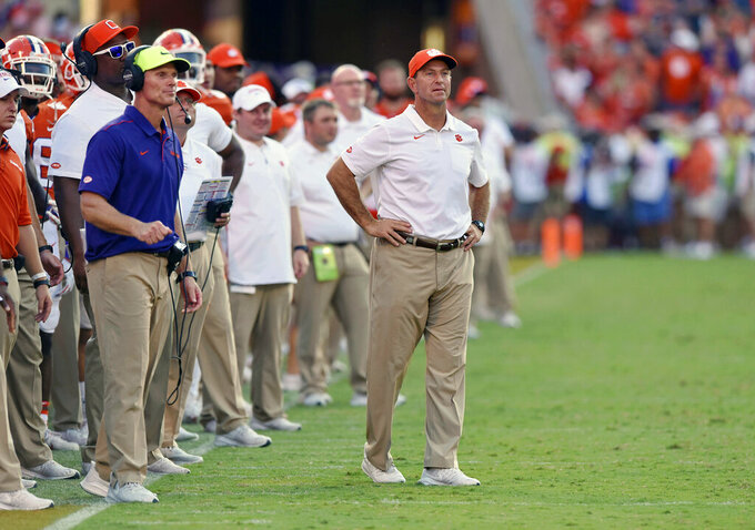 FILE - In this Saturday, Sept. 7, 2019 file photo, Clemson head coach Dabo Swinney, center, and defensive coach Brent Venables, left, watch the action during the second half of an NCAA college football game against Texas A&M in Clemson, S.C.  Tyler Davis didn't plan on starting this soon for Clemson, given the depth the Tigers had stockpiled at defensive tackle the past few seasons. Clemson coach Dabo Swinney and defensive coordinator Brent Venables had planned for the talent drain and had brought along several linemen like Williams and junior Xavier Kelly to take over. They didn't count on Davis forcing his way into the starting lineup. (AP Photo/Richard Shiro, File)