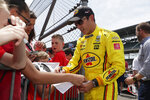 Helio Castroneves, of Brazil, signs autographs for fans during practice for the Indianapolis 500 IndyCar auto race at Indianapolis Motor Speedway, Thursday, May 16, 2019 in Indianapolis. (AP Photo/Michael Conroy)