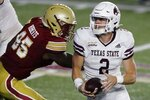 Texas State quarterback Brady McBride (2) tries to get away from  Boston College defensive end Max Roberts (95) during the first half of an NCAA college football game Saturday, Sept. 26, 2020, in Boston. (AP Photo/Michael Dwyer)
