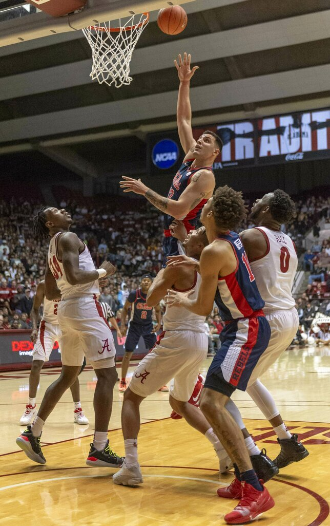 Mississippi center Dominik Olejniczak (13) shoots a hook for two above three Alabama defenders during the first half of an NCAA college basketball game, Tuesday, Jan. 22, 2019, in Tuscaloosa, Ala. (AP Photo/Vasha Hunt)
