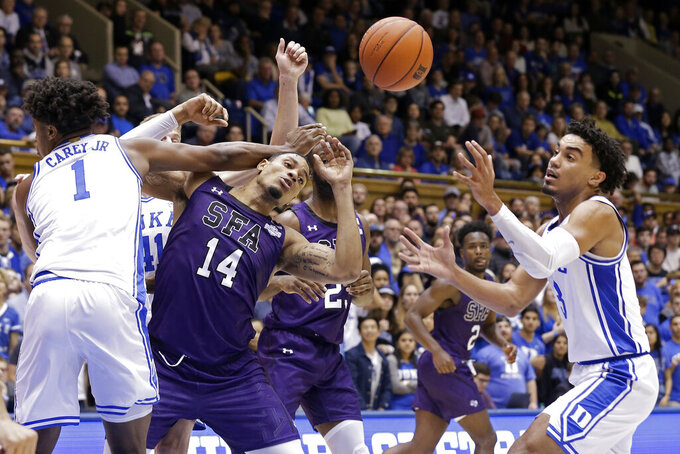 Duke center Vernon Carey Jr. (1) and guard Tre Jones, right, guard Stephen F. Austin forward Gavin Kensmil (14) during the first half of an NCAA college basketball game in Durham, N.C., Tuesday, Nov. 26, 2019. (AP Photo/Gerry Broome)