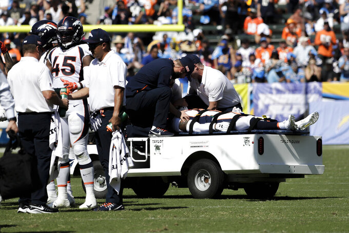 FILE - In this  Sunday, Oct. 6, 2019 file photo, Denver Broncos cornerback DeVante Bausby is taken off the field after being hurt during the first half of an NFL football game against the Los Angeles Chargers, in Carson, Calif. Broncos cornerback De'Vante Bausby says he was paralyzed for 30 minutes Sunday after he wrenched his neck colliding with linebacker Alexander Johnson while making a tackle on Chargers running back Austin Ekeler. (AP Photo/Alex Gallardo, File)