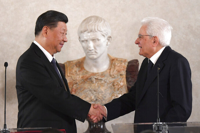 """Chinese President Xi Jinping shakes hands with Italian President Sergio Mattarella during a business forum inside the Quirinale Presidential, in Rome, Friday, March 22, 2019. Mattarella told visiting President Jinping on Friday that China's new """"Silk Road"""" linking Europe and Asia must be a """"two-way street,"""" addressing concerns among Western allies that the colossal infrastructure project is meant merely to amplify Beijing's influence in the region.  (Tiziana Fabi/Pool Photo via AP)"""