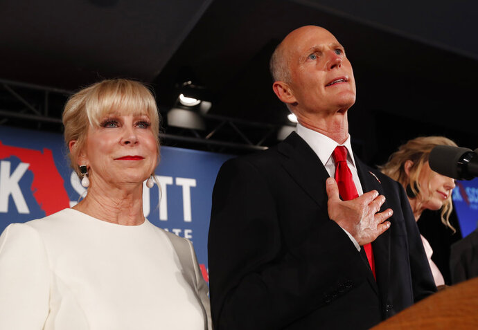 FILE- In this Wednesday, Nov. 7, 2018, file photo Republican Senate candidate Rick Scott speaks with his wife Ann by his side at an election watch party in Naples, Fla. Scott is leading incumbent Sen. Bill Nelson in the state's contentious Senate race. Official results posted by the state on Sunday, Nov. 18, showed Scott ahead of Nelson following legally-required hand and machine recounts. State officials will certify the final totals on Tuesday. (AP Photo/Wilfredo Lee, File)