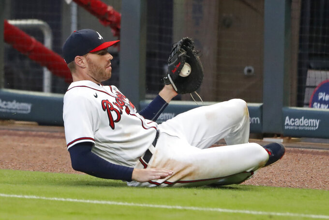Atlanta Braves first baseman Freddie Freeman (5) makes a sliding catch on a foul ball by Toronto Blue Jays Danny Jansen in the fifth inning of a baseball game Tuesday, Aug. 4, 2020, in Atlanta. (AP Photo/John Bazemore)