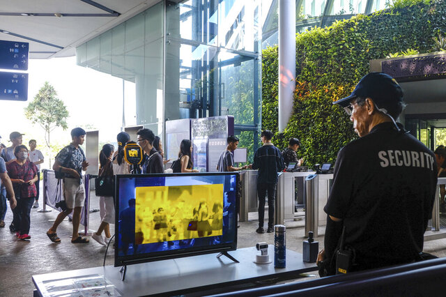In this March 14, 2020, photo, a security personnel views a thermal screening monitor as visitors enter Gardens by the Bay in Singapore. As the virus outbreak spreads ever further, it's becoming clear that some strategies are more likely to succeed in containing it: pro-active efforts to track down and isolate cases, access to basic, affordable public health and clear, reassuring messaging from leaders. (AP Photo/Ee Ming Toh)
