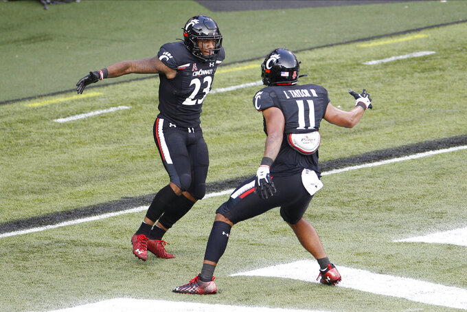 Cincinnati running back Gerrid Doaks, left, celebrates his touchdown against Army with teammate Leonard Taylor during the second half of an NCAA college football game Saturday, Sept. 26, 2020, in Cincinnati, Ohio. Cincinnati beat Army 24-10. (AP Photo/Jay LaPrete)