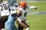 Cleveland Browns quarterback Baker Mayfield (6) gets a pass away as he is hit by Tennessee Titans cornerback Desmond King (33) in the first half of an NFL football game Sunday, Dec. 6, 2020, in Nashville, Tenn. (AP Photo/Ben Margot)