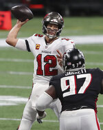 Tampa Bay Buccaneers quarterback Tom Brady (12) completes a pass under pressure from Atlanta Falcons defensive tackle Grady Jarrett during the fourth quarter of an NFL football game Sunday, Dec. 20, 2020, in Atlanta. (Curtis Compton/Atlanta Journal-Constitution via AP)