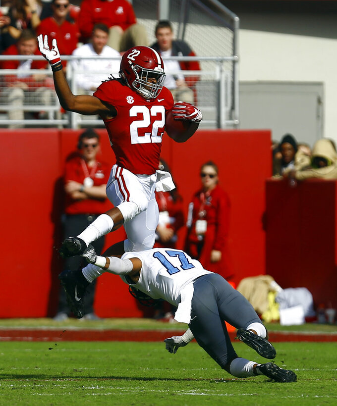 Alabama running back Najee Harris (22) hurdles Citadel defensive back Chris Beverly (17) as he carries the ball during the first half of an NCAA college football game, Saturday, Nov. 17, 2018, in Tuscaloosa, Ala. (AP Photo/Butch Dill)