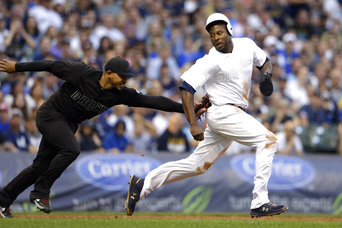 Milwaukee Brewers' Lorenzo Cain, right, is tagged out by Arizona Diamondbacks' Eduardo Escobar after being caught in a rundown during the third inning of a baseball game Saturday, Aug. 24, 2019, in Milwaukee. (AP Photo/Aaron Gash)