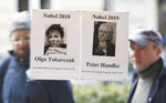 Two men pass by a bookshop in Warsaw, Poland, Thursday, Oct. 10, 2019. Polish author Olga Tokarczuk and Austrian author Peter Handke won the 2018 and 2019 Nobel Prizes for literature. Two Nobel Prizes in literature were announced Thursday after the 2018 literature award was postponed following sex abuse allegations that rocked the Swedish Academy at that time. (AP Photo/Czarek Sokolowski)