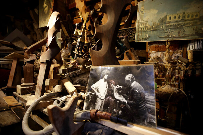In this photo taken on Sunday, Nov. 17, 2019, wooden objects lean on a shelf at the Paolo Brandolisio oars laboratory, during an interview with the Associated Press, in Venice, Italy. Venetians are fed up with what they see as an inadequate to the city's mounting problems: record-breaking flooding, damaging cruise ship traffic and over-tourism. They feel largely left to their own devices, and with ever fewer Venetians living in the historic part of the city to defend its interests and keep it from becoming a theme park or museum.(AP Photo/Luca Bruno)