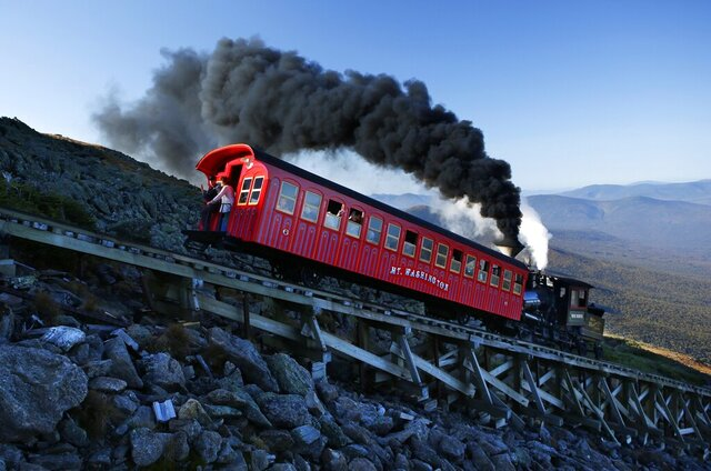 FILE - In this Sept. 24, 2017, file photo, a vintage coal-fired steam engine pushes a passenger car up the Cog Railway on a 3.8-mile journey to the summit of 6,288-foot Mount Washington in New Hampshire. A hiker descending Mount Washington on Sunday, March 22, 2020, who fell about 200 feet and was injured, was rescued with the help of the Cog Railway. (AP Photo/Robert F. Bukaty, File)