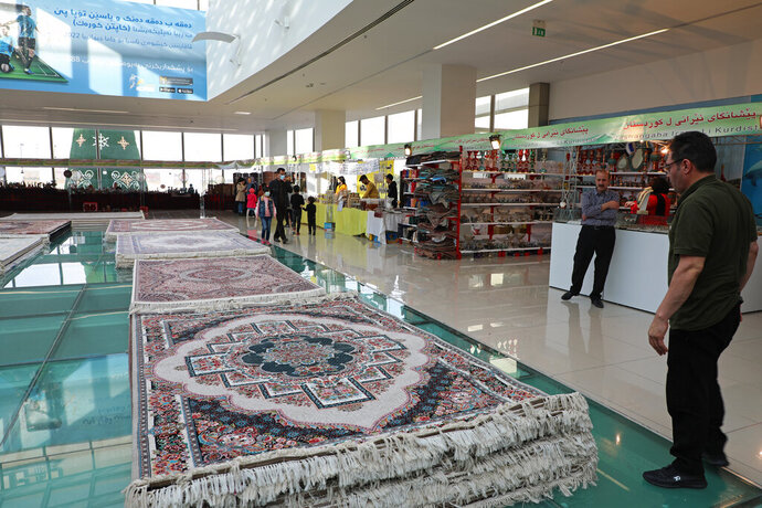 Piles of plush Iranian- made carpets line the floors of a shopping center in northern Iraq, hosting traders from neighbouring Iran, in the city of Dohuk, in the Kurdish-run northern region of Iraq, Wednesday, Jan. 20, 2021. At least 24 businesses from 15 Iranian cities offer hope that the spangle of their ornate handicrafts might offer a lifeline out of poverty for Iranians whose country's economy is in tatters amid crippling sanctions. (AP Photo/Rashid Yahya)