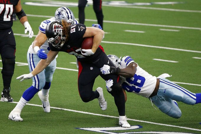 Atlanta Falcons tight end Hayden Hurst (81) is brought down by Dallas Cowboys' L.P. LaDouceur, left and linebacker Joe Thomas (48) in the first half of an NFL football game in Arlington, Texas, Sunday, Sept. 20, 2020. (AP Photo/Michael Ainsworth)