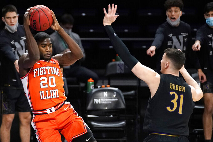 Illinois guard Da'Monte Williams, left, looks to pass the ball as Northwestern forward Robbie Beran defends during the first half of an NCAA college basketball game in Evanston, Ill., Thursday, Jan. 7, 2021. (AP Photo/Nam Y. Huh)