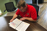 In this Wednesday, Oct. 9, 2019 photo, Swansboro Town Manager Chris Seaberg looks through a report commissioned by the town on the dangers of rising sea levels, in Swansboro, N.C. The report was prompted by a surprisingly high flood caused by Hurricane Florence in 2018 and says the town needs to act now as sea levels continue to rise because of climate change (AP Photo / Jeffrey Collins)