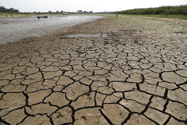 Cracked earth is exposed in the riverbed of the Paraguay River in Chaco-i near Asuncion city, Paraguay, Thursday, Oct. 8, 2020. The Paraguay River reached its lowest level in 50 years on Friday, Oct. 9, 2020, following months of extreme drought that has exposed the nation's economic dependence on the river and limited access to drinking water. (AP Photo/Jorge Saenz)