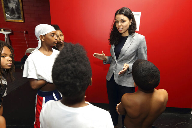 In this photo from March 10, 2020, Morgan Harper, Democratic candidate for Ohio's 3rd Congressional District running against Democratic four-term incumbent Joyce Beatty, talks with End the Violence participants at Elite Boxing Gym in Columbus, Ohio. (AP Photo/Paul Vernon)