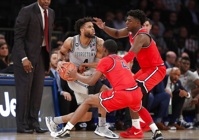 St. John's guard Greg Williams Jr., middle, and forward Marcellus Earlington (10) defend against Georgetown guard Jagan Mosely, left, during the second half of an NCAA college basketball game in the first round of the Big East men's tournament Wednesday, March 11, 2020, in New York. (AP Photo/Kathy Willens)