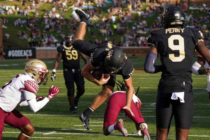 Wake Forest quarterback Sam Hartman, center top, dives into the end zone for a two-point conversion against Florida State during the second half of an NCAA college football game Saturday, Sept. 18, 2021, in Winston-Salem, N.C. (AP Photo/Chris Carlson)