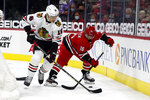 Carolina Hurricanes' Vincent Trocheck (16) is pestered by Chicago Blackhawks' Nikita Zadorov (16) behind the net during the second period of an NHL hockey game in Raleigh, N.C., Tuesday, May 4, 2021. (AP Photo/Karl B DeBlaker)