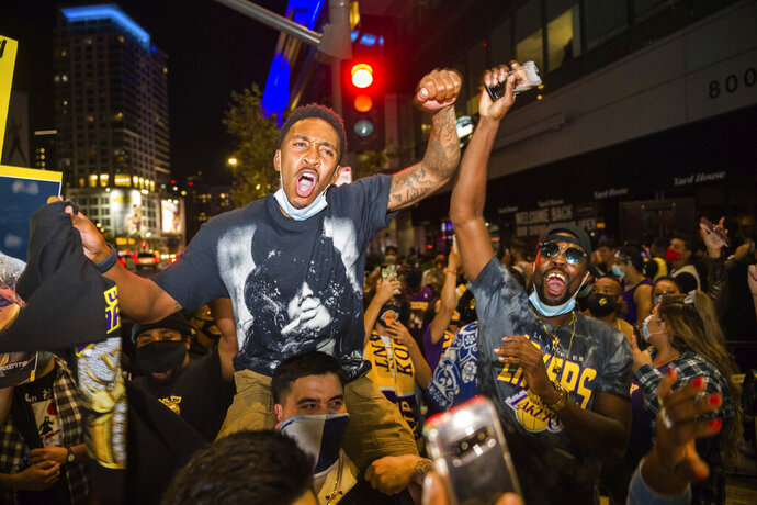 FILE - In this Oct. 11, 2020, file photo, fans in Los Angeles celebrate after the Los Angeles Lakers defeated the Miami Heat in Game 6 of basketball's NBA Finals to win the championship. A backlog in coronavirus testing results hid a recent rise in infections in Los Angeles County, the county's top health official said Monday, Oct. 26, 2020, warning that fans gathering to watch recent championship sporting events may have increased the spread. (AP Photo/Jintak Han, File)