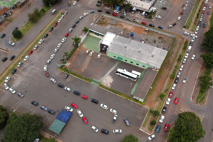A line of vehicles curls around a COVID-19 vaccination point for priority elderly persons in the Ceilandia neighborhood, on the outskirts of Brasilia, Brazil, Monday, March 22, 2021. (AP Photo/Eraldo Peres)